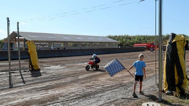 Det er 15. gang, Brovst Speedway Center lægger bane til sommercampen, hvor der ugen igennem trænes i mange forskellige teknikker og regler. Det ternede flag markerer eksempelvis, at løbet er færdigt, mens det røde betyder stop. - Børnene er seje, og hvis der opstår et lille uheld, er de hurtigt på cyklen igen, fortæller Alex Thomsen.