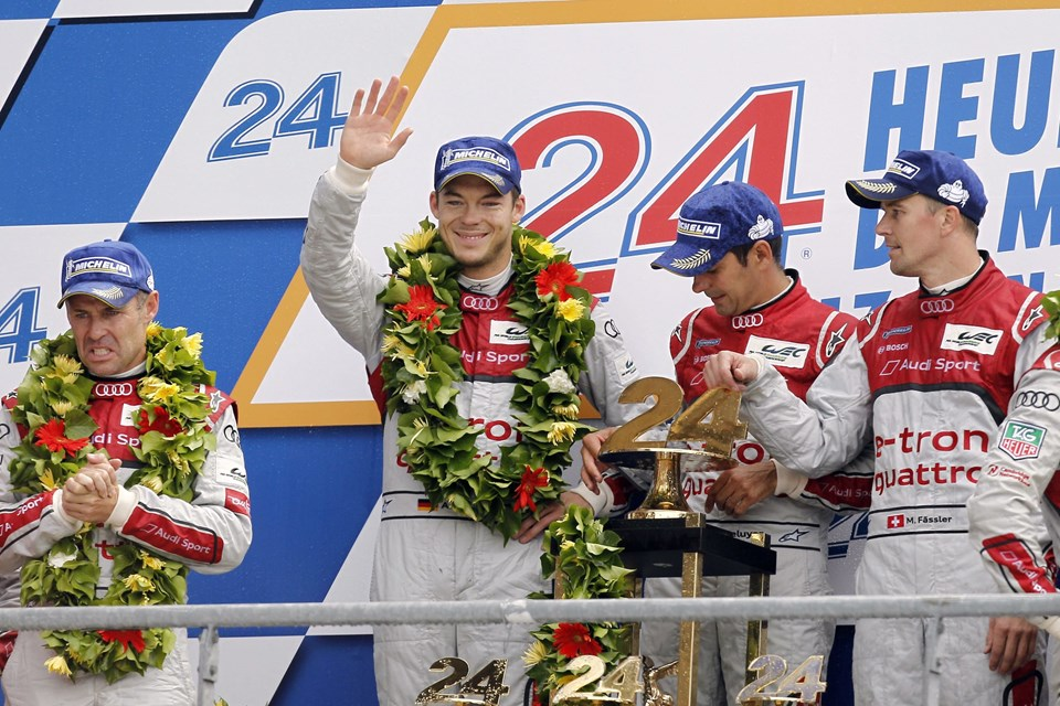 (LtoR) Drivers of the Audi R18 E-Tron Quattro Nº1, German Andre Lotterer, French Benoit Treluyer, Swiss Marcel Faessler, celebrate on the podium after winning the 80th edition of Le Mans 24 hours endurance race, on June 17, 2012 in Le Mans, western France. Audi have now won 11 of the last 13 races at Le Mans since 1999, while for the trio of Treluyer, Fassler and Lotterer it was a second win in succession. It was the first time that a hybrid car had won the prestigious race since its inception in 1923. AFP PHOTO / CHARLY TRIBALLEAU