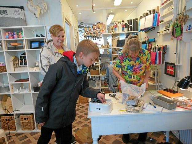 Britt Geisler byder kundens søn på bolsjer, mens gaven pakkes ind.