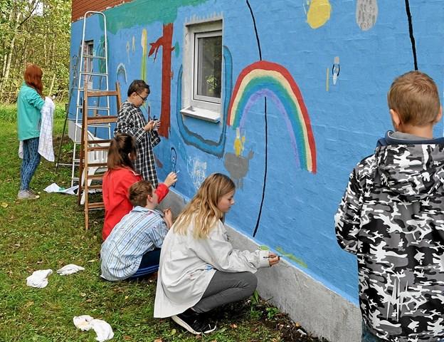 Så er murmaleriet i fuld gang. Muren har fået en blå bundfarve, inden eleverne gik i gang. Foto: Ole Torp