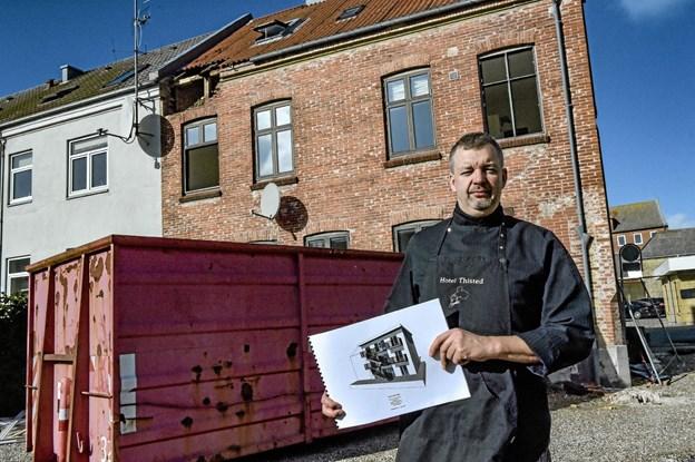 Michael Eriksen med tegningen over sydfacaden på bygningen der skal rejses, hvor den røde murstensbygning står - nogle dage endnu. Nedrivningen er i gang. Foto: Ole Iversen