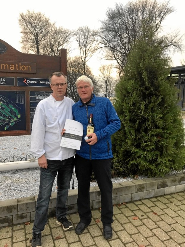 Restauratør Jan Thomassen, Mariagerfjord Golfklub, overrækker gavekort og whiskey til John Jørgensen. Privatfoto