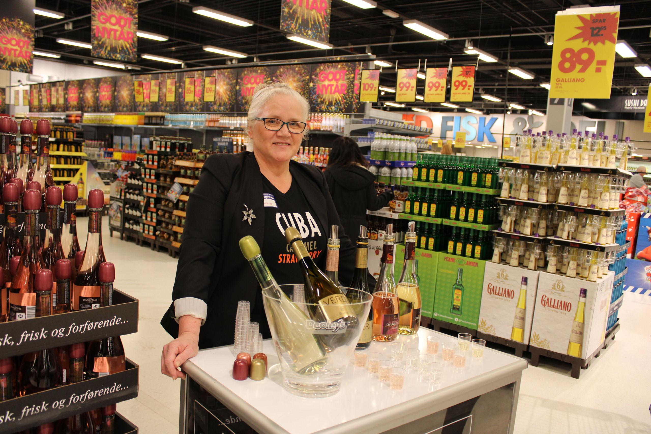 Connei Eriksen uddeler smagsprøver af de våde varer til nytåret. Foto: Pauline Vink