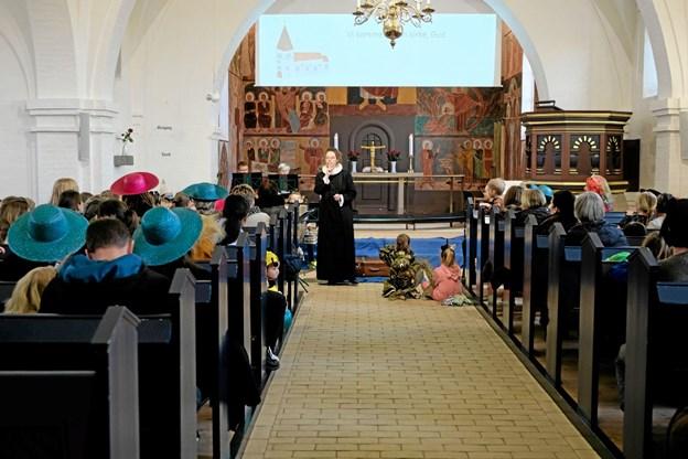 Sognepræst Iben Aldal tysser på børnene. Nu skal de være stille og lytte til kirkeklokkerne. Foto: Niels Helver Niels Helver