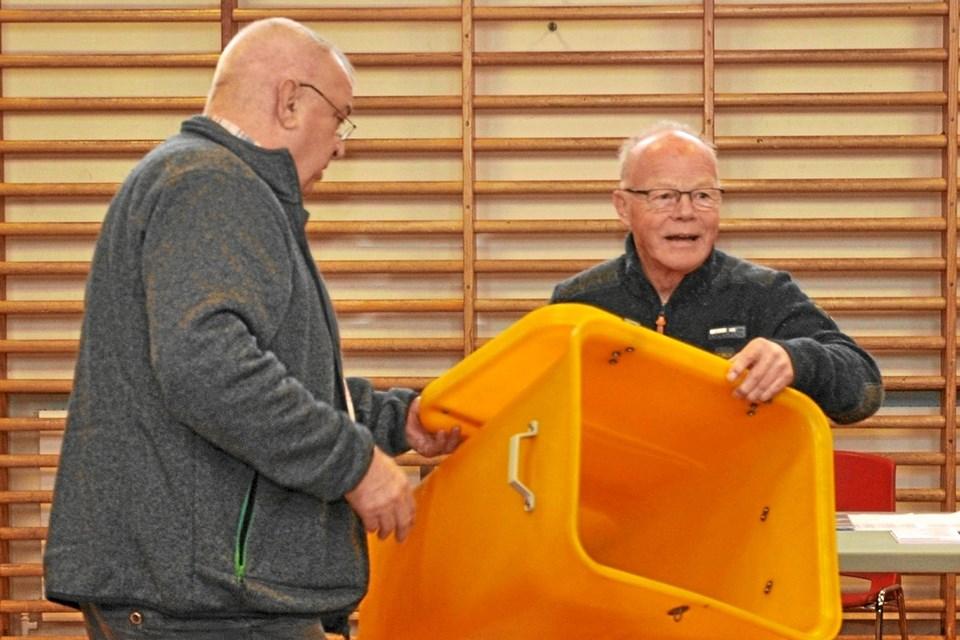 De to tilforordnede, Erik Østergaard (t.v.) og Thorkild Kroer, var meget omhyggelige i deres kontroller. Her sikrer man sig, at stemmeurnen er totalt tom, inden valget for alvor starter.Foto: Ole Torp