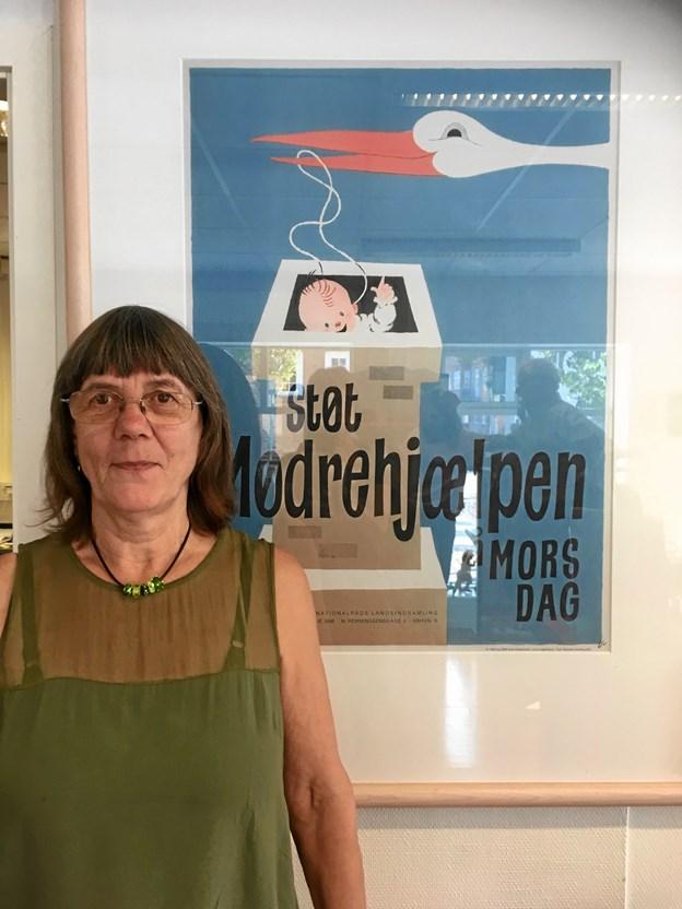 Lis Hillgaards datter foran plakaten som nu hænger i Mødrehjælpens forretning. Privatfoto
