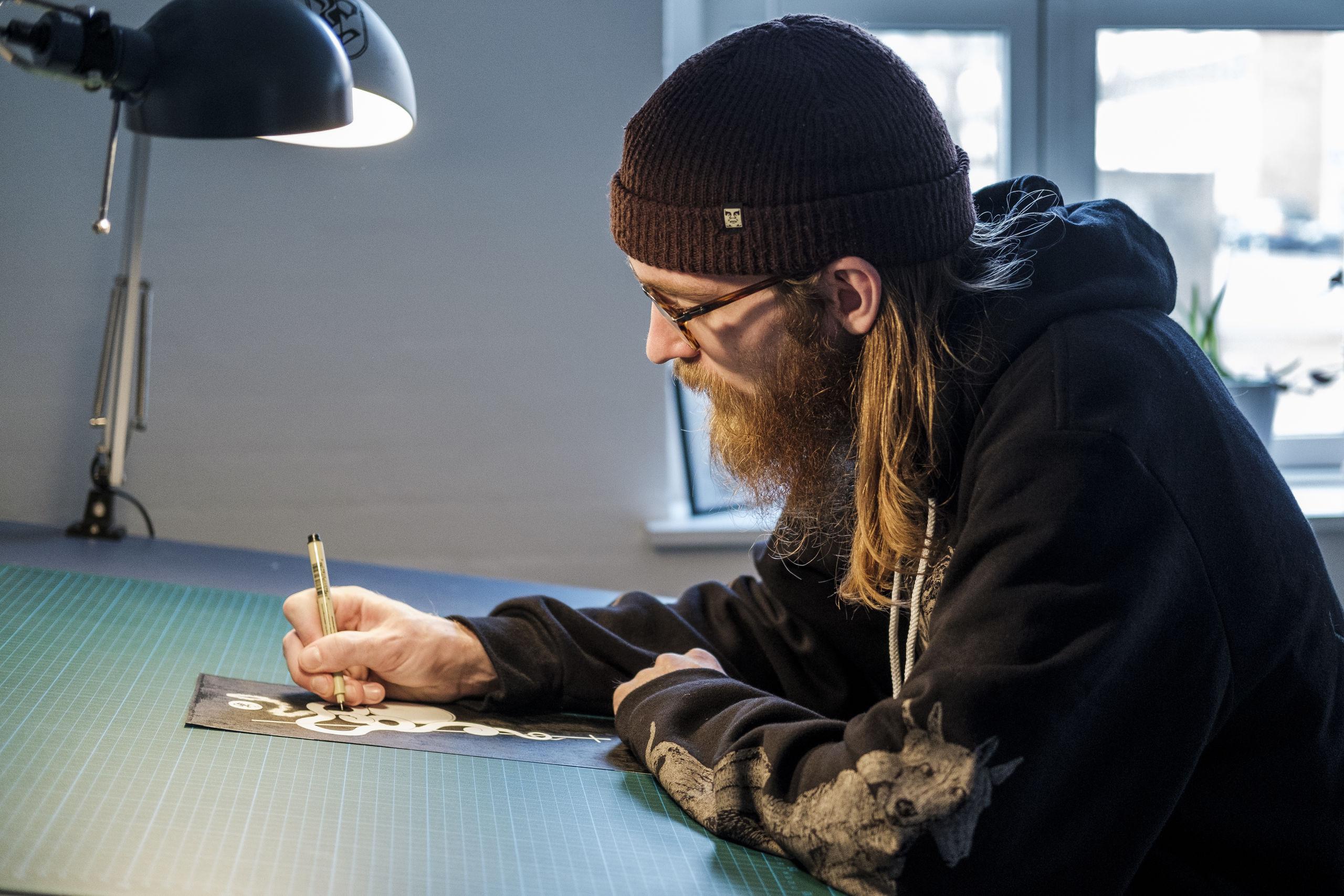 Ofte bliver han så grebet af arbejdet, at han sidder i flere timer og tegner. Men det ensformige arbejde er hårdt for hånden og øjnene. Foto: Lasse Sand