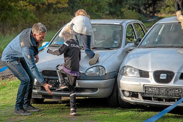 Den første forhindring er gamle skrotbiler, som børnene skal passere. Foto: Niels Helver