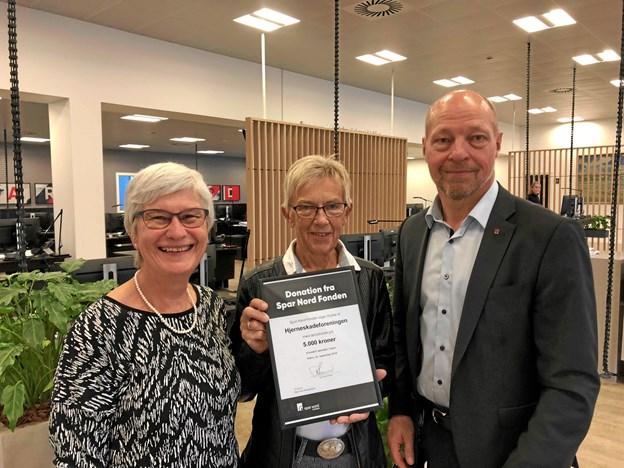 Direktør Frank Kristensen (t.h.) fra Spar Nord Bank  overrækker donationen på de 5000 kr. til  kasserer Sonja Svejstrup (i midten)  og formand Tove Swartz (t.v.) fra Hjerneskadeforeningen Himmerland. Privatfoto