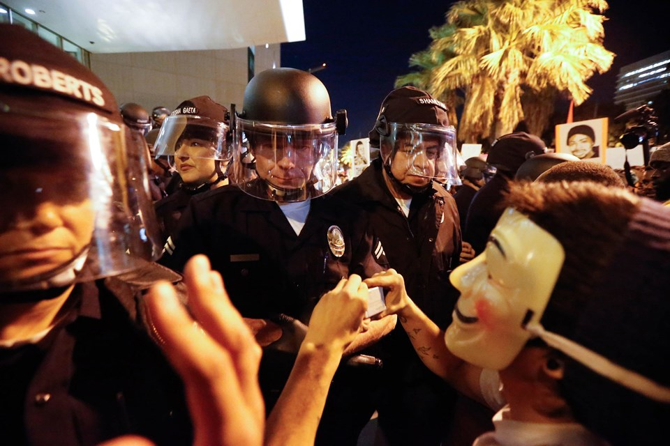 Politi og en maskeret demonstrant i Los Angeles. Foto. Scanpix