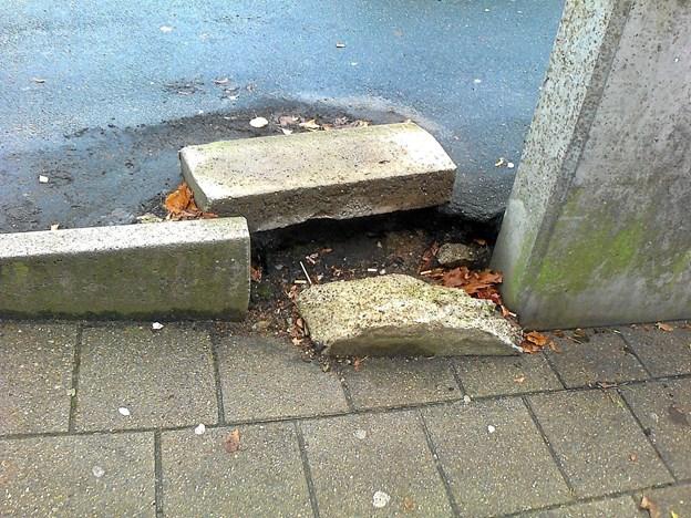 Kantstenen mellem parkeringspladsen og gangstien langs butikkerne i Gistrup er ved at forfalde. Privatfoto