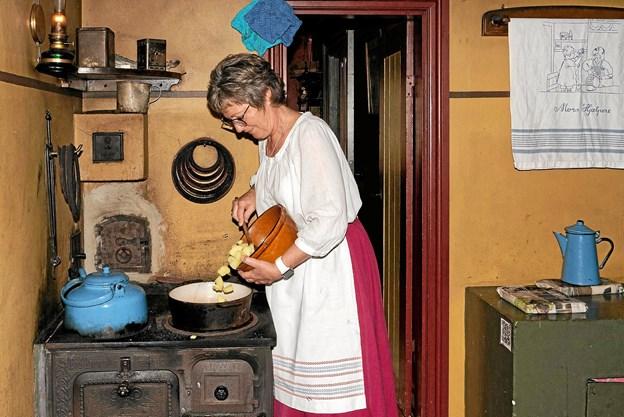 Vibeke Bak Jensen tilbereder kartoffelsuppe, der serveres som smagsprøver til publikum. Hun er i god træning med det gamle komfur, da hun sammen med sin mor og datter samt hendes børn var husmandsfamilie i uge 30. Foto: Niels Helver