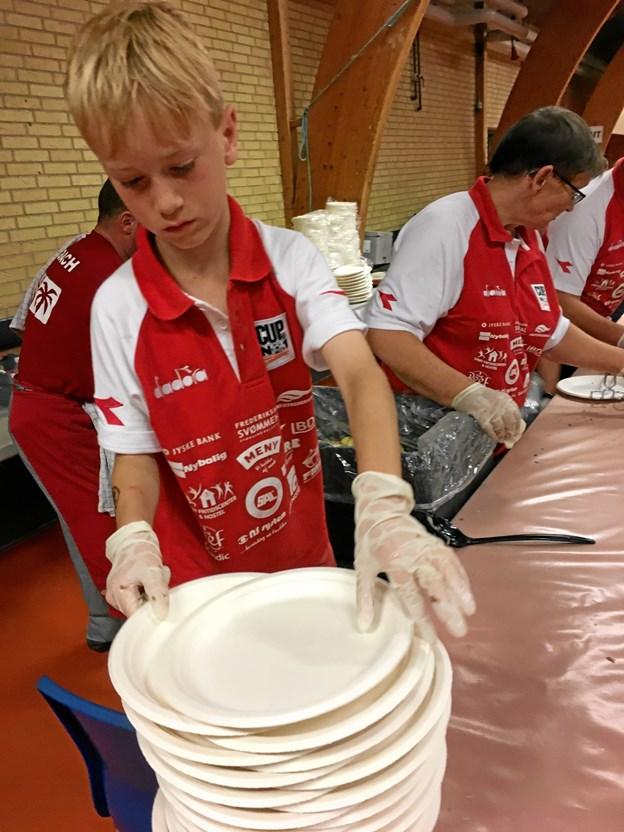 Friske unge hjælper til med tallerkener.