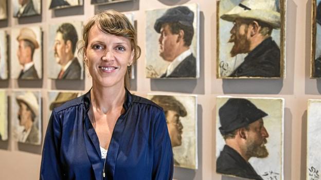 Direktør Lisette Vind Ebbesen, Skagens Kunstmuseer foran de berømte portrætter, hvor man kan se P.S. Krøyer i baggrunden med den hvide hat. Arkivfoto