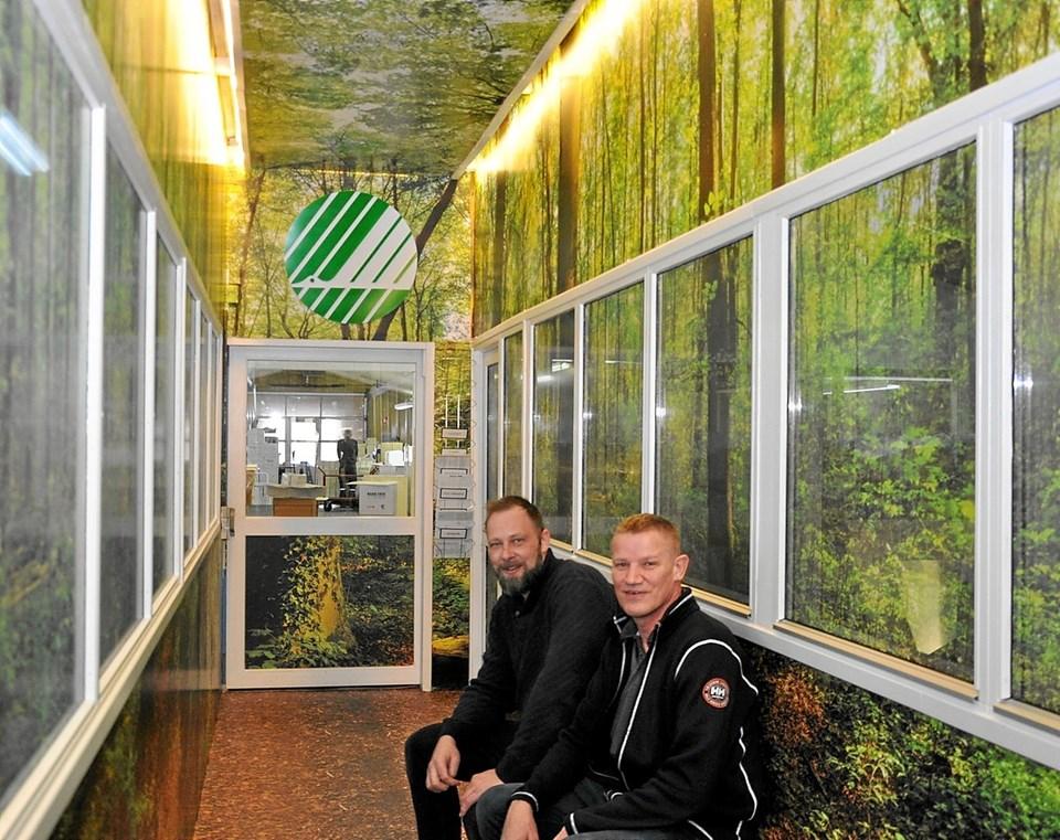 Christian Danielsen (t.v.) og forretningsforbindelsen Bjarne Haun sidder inde i en af gangene, hvor siderne er beklædt med det nye digitale tapet, så man faktisk har fornemmelsen af at være i en skov. Foto: Ole Torp