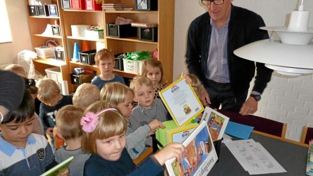 Formanden for menighedsrådet i Gistrup, Nils Dorin Jacobsen, uddeler boggaver til børnene døbt i årene 2012-2014. Foto: Kjeld Mølbæk Kjeld Mølbæk