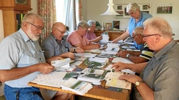 Der pakkes og ordnes ved bordet, hvor de nytrykte programmer for Ældre Sagen Mors er klar.