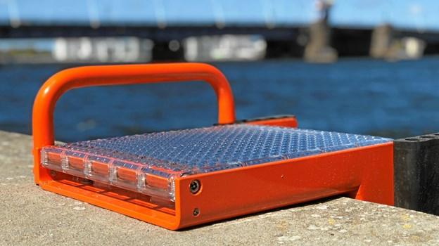 Den firkantede platform, der er monteret på selve kajkanten, er fyldt med solceller, og det betyder, at redningsstigerne er oplyste i aften- og nattetimerne. Foto: Henrik Poulsen