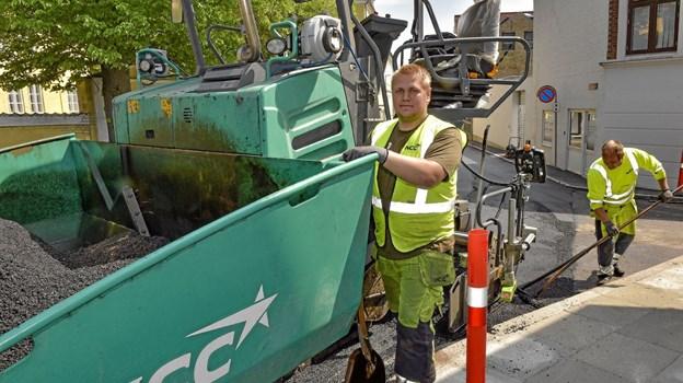 Maskinfører Lasse Poulsen fra asfaltfirmaet NCC lover, at han lægger et fint to cm. tykt lag asfalt, så Skovgade bliver en ny fornøjelse at køre på. Foto: Ole Iversen