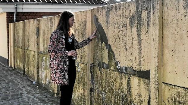 Lise Vestergaard ved den noget ramponerede mur i Løkken som kommer til at bære et kunstværk. Muren findes på Jens Bangs Sti der forbinder Torvet og Møstingsvej. Foto: Privatfoto Privatfoto