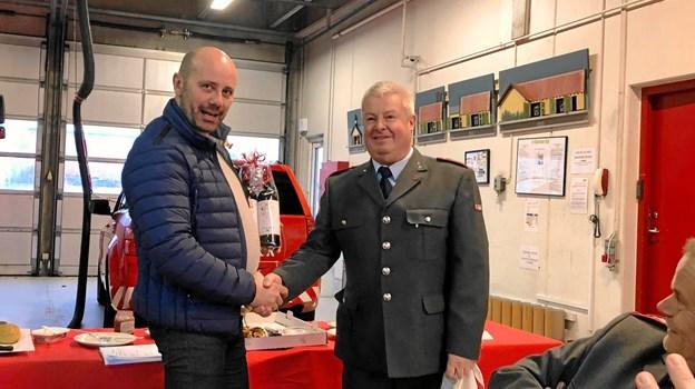 Brandstationsleder Henrik Kristensen t.h. siger tillykke til Tony Jespersen der vandt 2018 præmien for rigtig gæt på antal udkald. Privatfoto