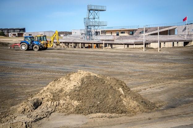 Bunden skal skrabes fri for snavs, inden der bliver lagt nyt strandsand på overfladen.