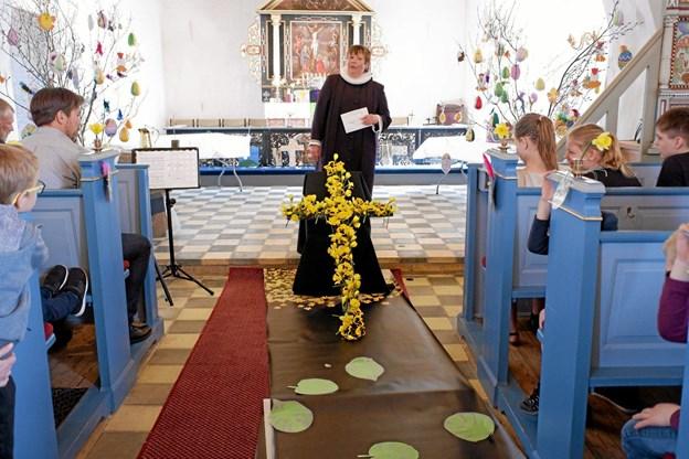 Efter eleverne har pyntet korset med påskeliljer holder Eva Christophersen påskeprædiken om Jesus lidelser. Foto: Niels Helver Niels Helver