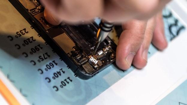 Ulrik Larsen og Stefan Christiansen reparerer mobiler med bittesmå værktøjer, der kan nå selv de mindste dimser i mobilen.