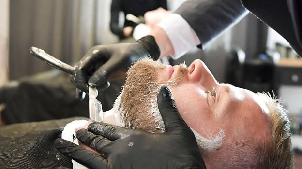 Grundlæggerne bag Frederic Hector vil give kunderne mulighed for at se godt ud hele tiden. Her er det master barber Rasmus Luther, som sørger for en barbering med kniv.  Foto: Michael Koch