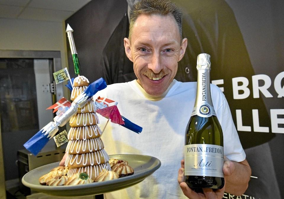 Jan bager fra SuperBrugsen sætter med en kransekage til 10 personer (mindre kransekagevist på billedet) og to flasker Asti til at drikke til rådhusklokkerne. Værdi 400 kroner. Foto: Ole Iversen Ole Iversen
