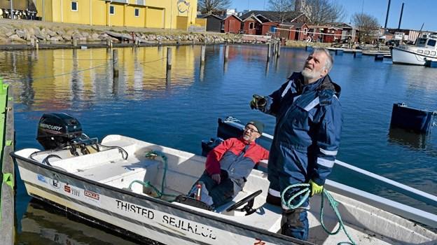 Der er ikke noget stress på i servicejollen Misse. Her tager Eigil Poulsen (rød) og Benny Madsen en slapper, indtil de skal flytte rambukflåden til et nyt sted i havnen.Foto: Ole Iversen Ole Iversen