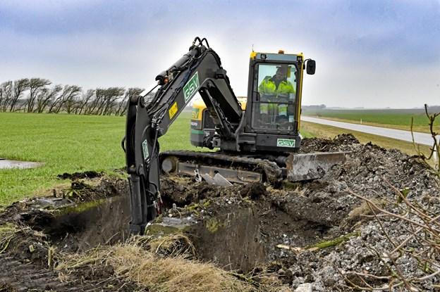 Mange landmænd bliver glade når der ikke længere skal køres udenom soklerne i marken. Her graves der fri, før nedbrydningshammeren kommer. I baggrunden omfartsvejen. Foto: Ole Iversen Ole Iversen