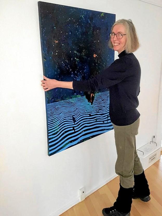 Eva Dalby-Jacobsen med maleriet 'Horisont Vertikal', hvortil er brugt en for hende ny malemetode med spartel og svamp. Foto: Karl Erik Hansen Karl Erik Hansen