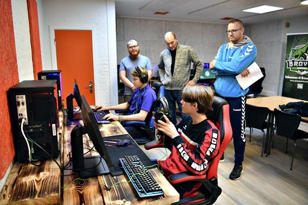 Der er allerede gang i computerne i det nye lokale, hvor Esport Brovst skal holde til. Drengene Tobias Busk (i blå trøje) og Sebastian Busk (i rød trøje) har fundet sig godt til rette i de nye omgivelser. Deres far, Stefan Busk (th), halinspektør Lars Simonsen og tovholder for Esport Brovst, Steffen Fisker, ser til, mens drengene tester gearet. Foto: Kurt Bering