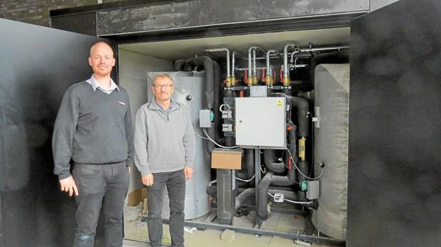 Kristian Bast og Kjeld Emil Damsgaard ved anlægget, som sender overskudsvarme fra Meny Løkken ud i Løkken Fjernvarmeværks rør. Foto: Kirsten Olsen