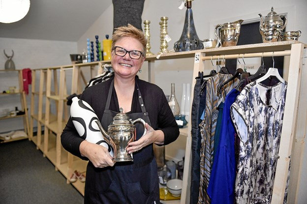 """Hanne Madsen ved en af """"sponsor-reolerne"""". Pengene fra salget af disse ting doneres til lokalsamfundet. Foto: Ole Iversen"""