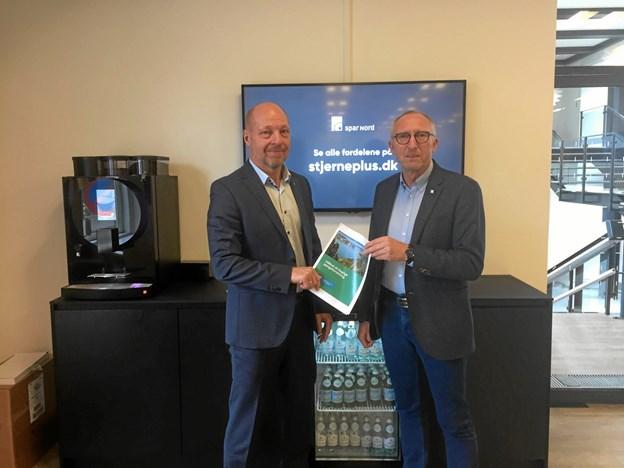 Borgmester Mogens Jespersen og direktør i Spar Nord Frank Kristensen giver hinanden hånden på, at Spar Nord Bank overtager Mariagerfjord Kommunes bankforretninger.    Privatfoto