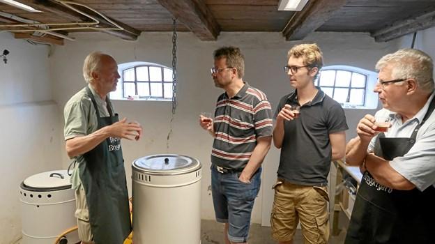 Lars Heiring (tv) fra Bryggerimuseets håndbryggerlaug forklarer et par udenlandske gæster om bryggeprocessen, mens Jacob Ranum (th) lytter med.