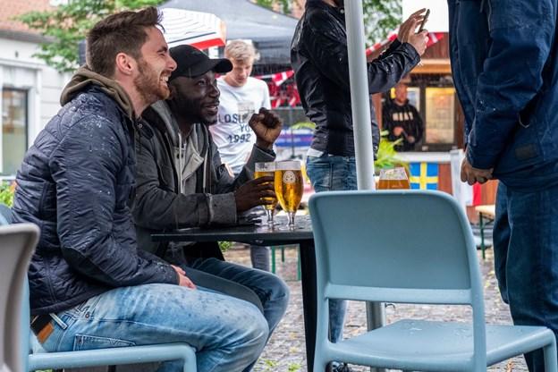Humøret var trods regnen o.k. Måske var det fordi de unge mænd ved dette bord spillede på sejr til Rusland. Foto: Lasse Sand