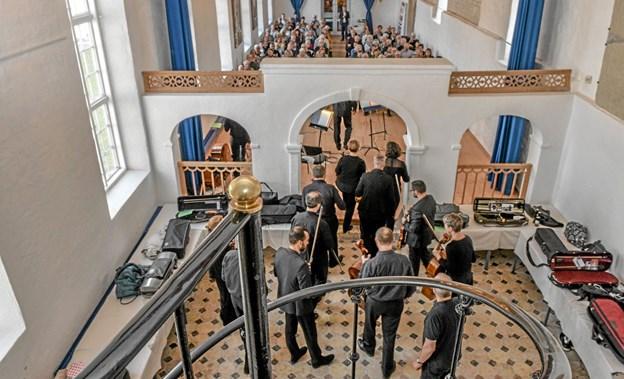Aalborg Symfoniorkesters strygere går ind for at møde publikum i kirkesalen på Vitskøl Kloster. Foto: Mogens Lynge
