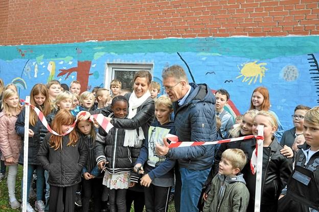 Borgmesteren og udvalgsformanden klipper med hjælp fra elever båndet over og markerer dermed ferniseringen. Dele af den nordiske mytologi ses bag dem. Foto: Ole Torp