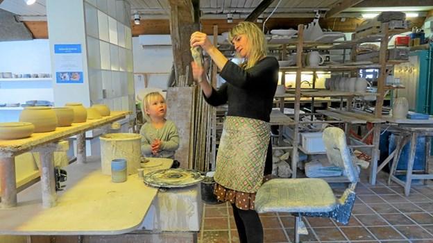Vibe Falkenberg viser en lille gæst, hvordan man laver en hank til et krus. Foto: Kirsten Olsen