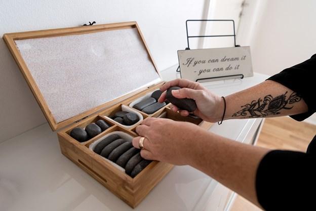 Hot stone behandlinger er en af de behandlinger, Rikke Søndergaard tilbyder. Bemærk skiltet med et motto, Rikke Søndergaard gerne husker sig selv på.