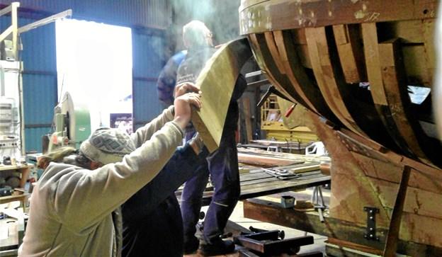 Gøl-Båden har medvind - netop nu i form af 100.000 kroner fra Augustinus Fonden. Her arbejder skibstømrere fra Han Herred Havbåde sammen med frivillige fra træskibslauget om at beklæde båden med dampbøjede egeplanker - et job, der kræver både snilde og kræfter. Foto: Jørn Hjerresen $ID/NormalParagraphStyle: