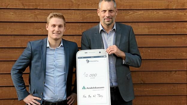 Tommy Pedersen modtager her 10.000 kroner fra Jesper Elkær, Andelskassens filialdirektør i Koldby. Privatfoto