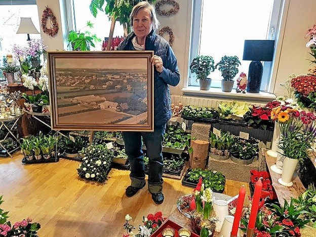 Kirsten Dahl med det historiske luftfoto i den nutidige butik. Foto: Karl Erik Hansen Karl Erik Hansen
