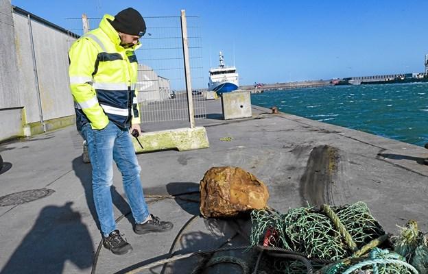 Det er heldigvis stabilt sprængstof, da der ikke længere er detonator i, forklarer havneassistent Peter Dyrby. Den brune klump sprængstof fra en tøndemine vejer 20-25 kilo. Foto: Ole Iversen Ole Iversen