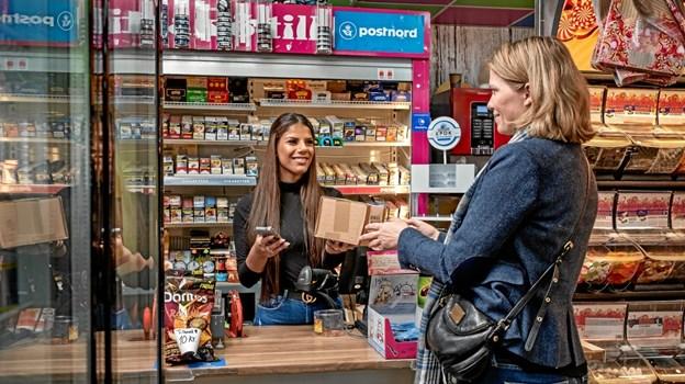 Tiffany Christensen udleverer en pakke til en kunde i butikken Den Søde Tand i Herlev, som er et af de 500 nye udleveringssteder for PostNord.Foto: Henrik Petit