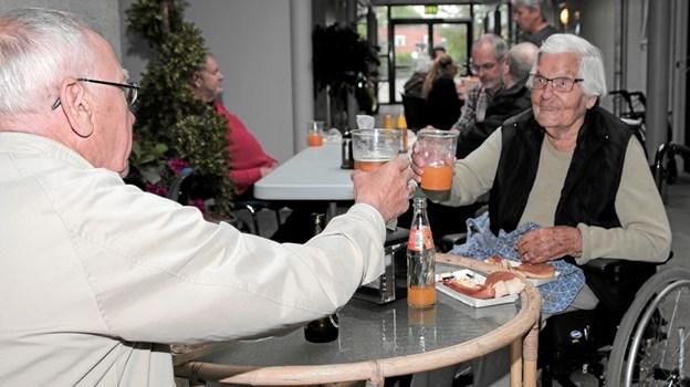 Agnes Johanne Westmark der snart fylder 100 år, skålede med Johannes Jensen, som er en af de mange frivillige. Foto: Peter Jørgensen Peter Jørgensen