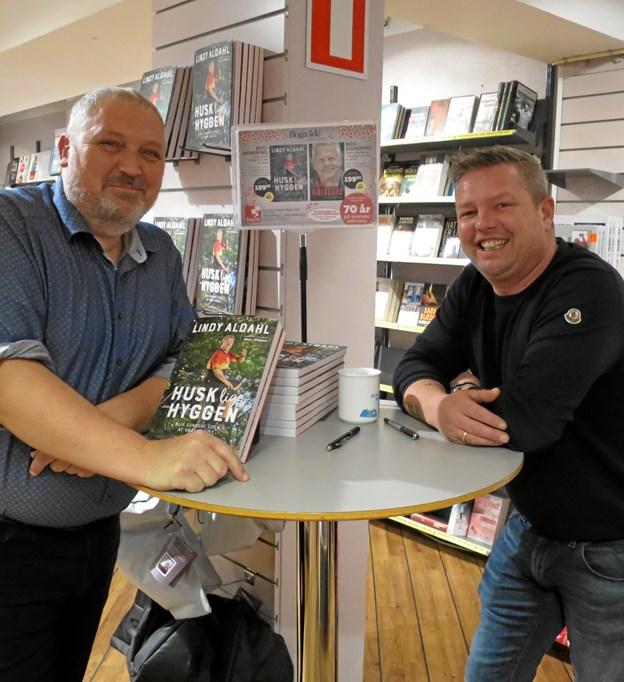 """Lindy Aldahl, en af de """"Rigtige Mænd"""" besøgte tirsdag 4. december Bog & Ide i Hadsund. Her kunne man få en snak med Lindy om hans nye bog """"Husk lige hyggen"""", og få den signeret. Mellem signeringerne var der et lille pusterum, hvor Bent Volmar fra Bog & Ide og Lindy Aldahl fik sig en hyggesnak. Dagen efter var Jakob Kjeldbjerg i butikken for at signere sin nye bog: """"Survivor"""". ?Foto/tekst: hhr-freelance.dk"""